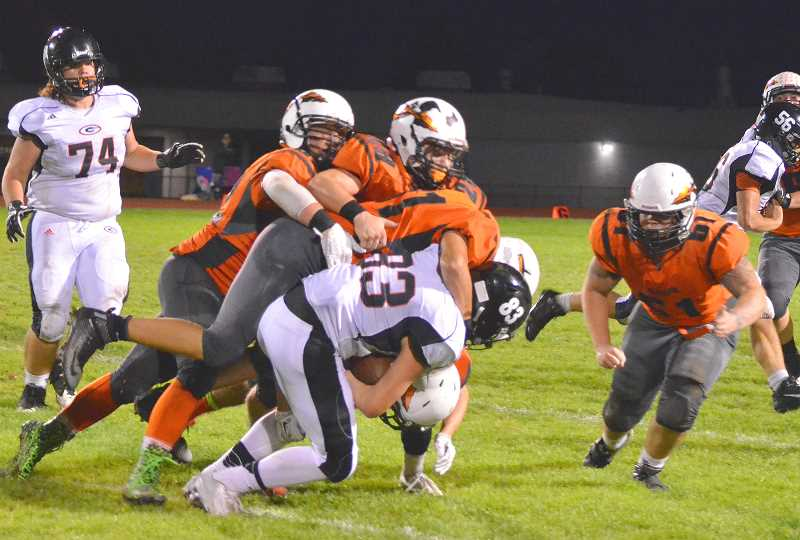 SPOTLIGHT PHOTO: JOHN BREWINGTON - The Scappoose defense was as stingy Friday as the offense was prolific. Colton Bird (28), Mason Reardon (21) and one other player gang-tackle Gladstone's Devin Neer.