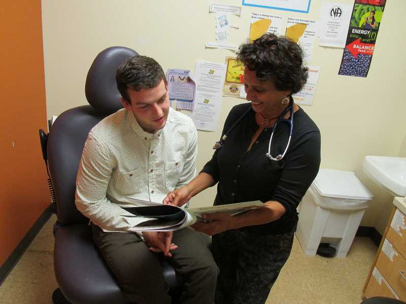 OUTLOOK PHOTO: ROB CULLIVAN - Dr. Anna Jimenez, right, uses easy-to-read booklets to help her patients understand their conditions and how to treat them.