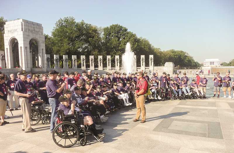 OUTLOOK PHOTO: SHANNON O. WELLS - Erik Tobiason, center, president of Honor Flight of Portland, corrals a group of 50 Oregon-based veterans and their guardians at the National World War II Memorial on the National Mall in Washington, D.C., on Friday, Sept. 18. The memorial was the first among several visits to military-related monuments and sights in the nations capital.