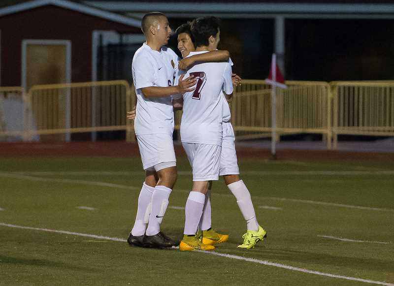 NEWS-TIMES PHOTO: KENT FRASURE - Jesus Gonzalez (6) and Murillo Oliveira (7) embrace Forest Grove teammate Diego Gaspar-Perez after he scored the Vikings first goal on a penalty kick during a 3-1 win at home against Newberg last Thursday.