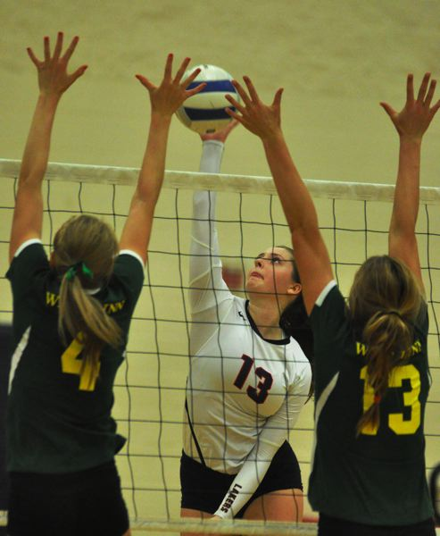 MATTHEW SHERMAN - Lake Oswego's Sarah Lewis looks to split a pair of West Linn blockers during the Lakers' four-set victory on Tuesday that moved them into second place in the TRL.