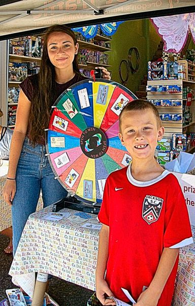 RITA A. LEONARD - At the free prize wheel for customers shopping on S.E. 13th Avenue on the day of the MAX opening were Cleveland High student volunteer Effie Purcell, and contestant Henry Sutter, age 7.