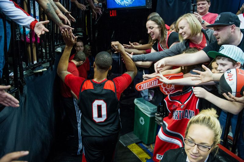 TRIBUNE PHOTO: JOHN LARIVIERE - Trail Blazers guard Damian Lillard connects with fans as he exits the court after Sunday's annual Fan Fest scrimmage at Moda Center.