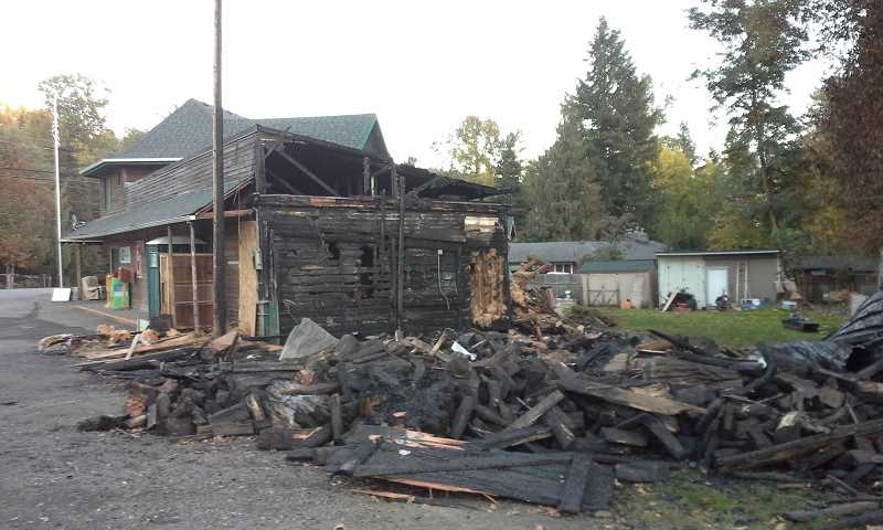 NEWS-TIMES PHOTO: JILL REHKOPF SMITH - A charred jumble of shingles and wood sits across the road from the unstaffed Gales Creek Fire Station. Three interns might be living (rent-free) at the station by the end of October, but that will be too late for the structures that burned last Friday.
