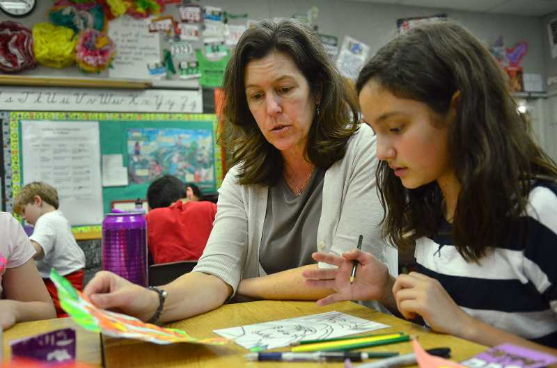 REVIEW PHOTO: VERN UYETAKE - Fourth-grader Juliette Marquez gets some help from teacher Dana Russell at Lake Grove Elementary School. Report Cards released Oct. 15 show the Lake Oswego School District is outperforming the rest of the state in helping its students grow academically.