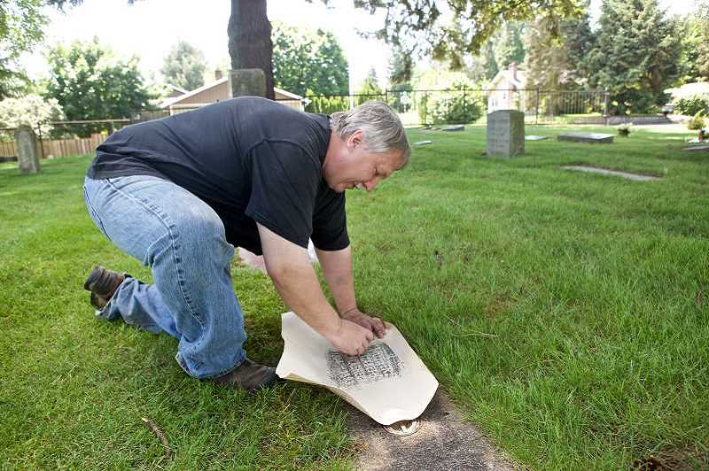 Jim Haberski, cemetery director at St. Anthony Catholic Cemetery, makes a rubbing of the cemetery's oldest headstone: Elizabeth Schlagheck, 1814-1893. The city of Tigard is hosting a walk around the city's cemeteries on Oct. 31.