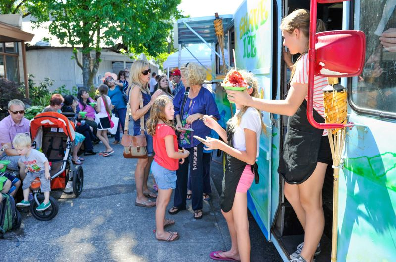 FILE - The Pupu Shack, a Hawaiian shave ice food truck, serves customers at the Downtown Tigard Street Fair in 2013.