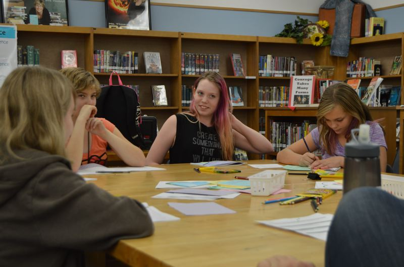 SPOTLIGHT PHOTO: NICOLE THILL - Molly James, an eighth-grader, and Wendy VanWinkle, Autumn Bush and Keleigh Thomas, all seventh-graders sit around a table during the workshop on Tuesday, Oct. 27. Bush shared a journal entry that she wrote with the group.