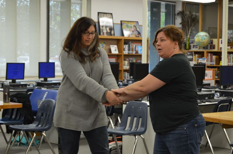 SPOTLIGHT PHOTO: NICOLE THILL - Danielle Speiser, language arts teacher, and Jill Griffin, school counselor, demonstrate how to break free from a wrist grab. During the workshop, students learned various self-defense techniques and practiced them each session.