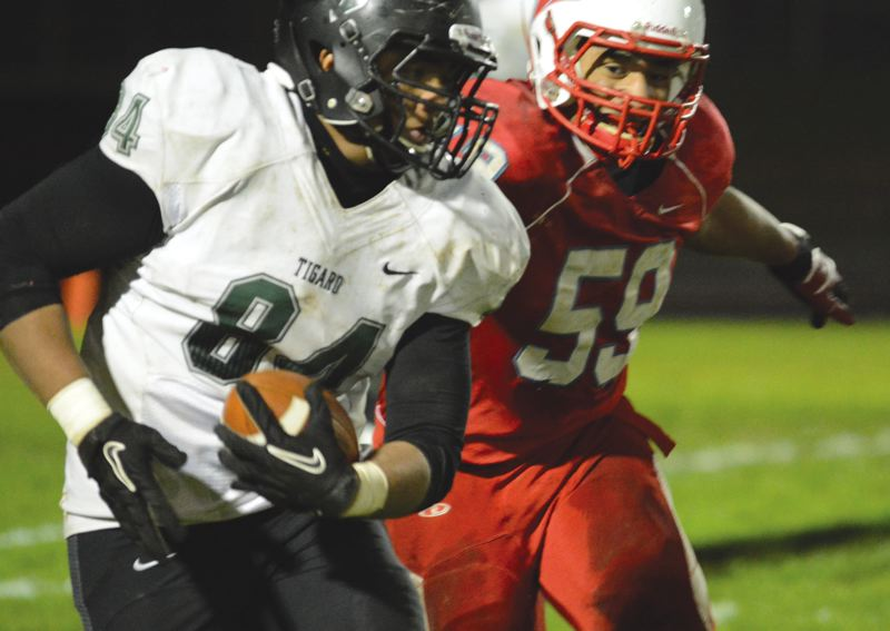 THE OUTLOOK: DAVID BALL - Centennials Raymond Fanene reaches out to bring down Tigard tight end Jossa Manners during the Tigers 34-22 playoff win Friday.