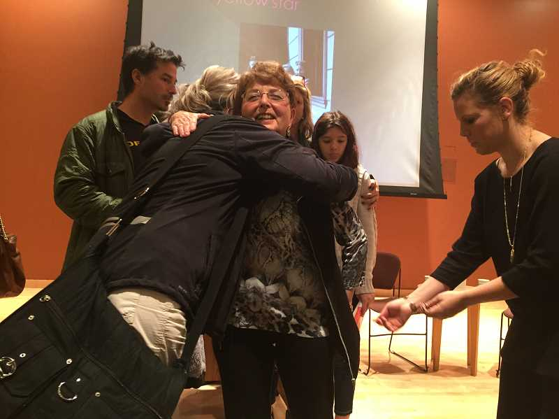 TIMES PHOTO: GEOFF PURSINGER - Eva Aigner hugs a library patron after her talk at the Tigard Public Library on Monday. The Holocaust survivor and her husband have been speaking out about the atrocities since the 1980s