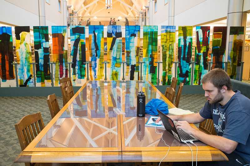 NEWS-TIMES PHOTO: CHASE ALLGOOD - Pacific University senior Jack Michels studies at the massive glass-topped table made by master craftsman Mike Johnson in 1999. The table sits on the second floor of the campus library, overlooking a grove of white oak trees.