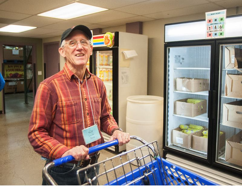 OUTLOOK PHOTO: JOSH KULLA - Longtime SnowCap volunteer Doug Medler shops with clients in SnowCaps warehouse, even taking their groceries to the car if they need help.