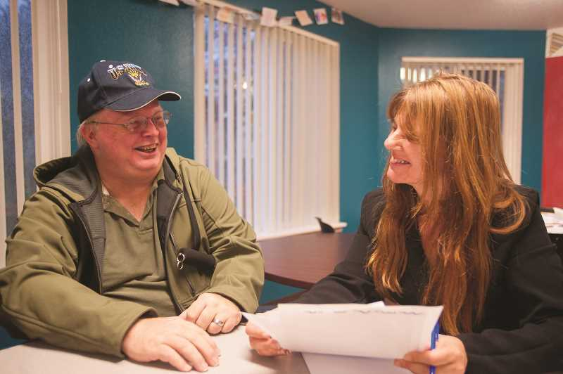 OUTLOOK PHOTO: JOSH KULLA - Gary Williams and Dina DiNucci share a laugh during a recent consultation at the Rockwood Station apartments, where DiNucci visits weekly to help enroll residents in availalbe health care plans.