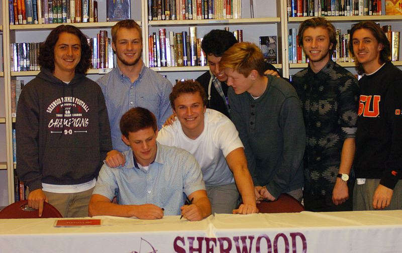 DAN BROOD - Sherwood senior Adley Rutschman, surrounded by some of his Bowmen teammates, signs his letter of intent to play baseball at Oregon State University.
