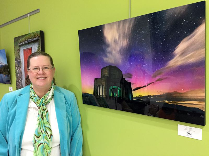 SUBMITTED PHOTO - Dawn Baker, a member of Women Learning Photography Together, stands next to her image Crown Vista Aurora during the artists reception at The Beaverton Building on Nov. 10.