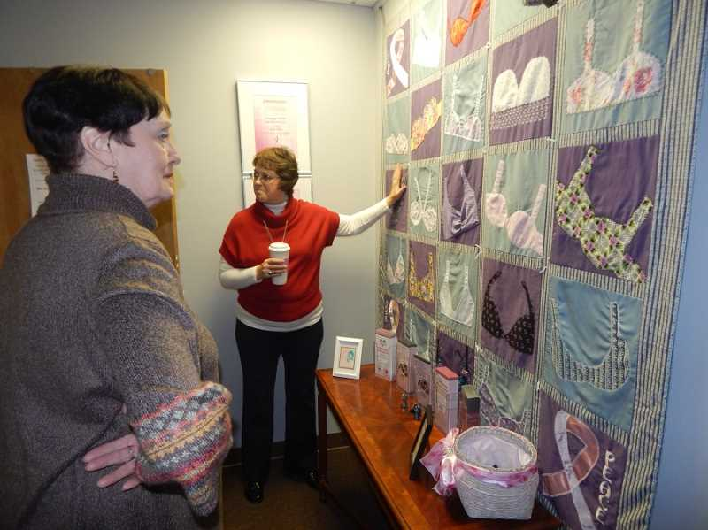 BARBARA SHERMAN - Sharon Henifin (right) of Breast Friends describes to Carlene Simmering and others the history of this bra-themed quilt.