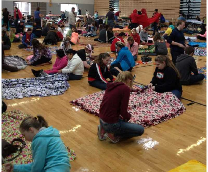 PAMPLIN MEDIA GROUP - Students and families gather once a year to assemble fleece blankets for homeless students in the school district.