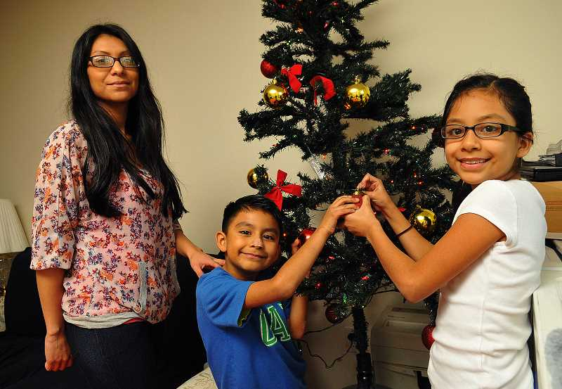 REVIEW PHOTO: VERN UYETAKE - Jacqueline Adan and her two children, Obadiah, 6, and Angelica, 9, decorate their tree in the apartment where they now live after transitioning out of homelessness with the help of the Lake Oswego Transitional Shelter Ministry. The nonprofit not only houses families, but also provides transportation, education and other assistance.