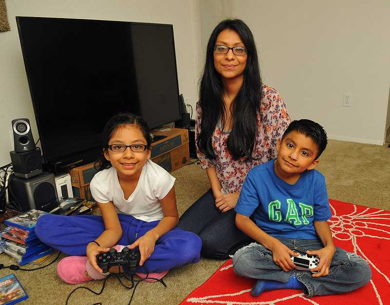 REVIEW PHOTO: VERN UYETAKE - Jacqueline Adan and her children, Angelica, 9 and Obadiah, 6, relax in their Oregon City apartment. The Lake Oswego Transitional Shelter Ministry housed them in one of the two apartments they offer to famlies in need who are trying to move from the streets or a homeless shelter into their own permanent living arrangement.