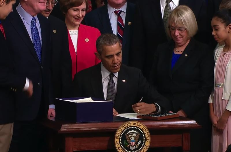 SCREEN SHOT OF WHITEHOUSE.GOV VIDEO - Oregon Rep. Suzanne Bonamici (in red) stands behind President Barack Obama and Washington Senator Patty Murray stands to the right as he signs the Every Student Succeeds Act, legislation eight years overdue after No Child Left Behind expired in 2007.