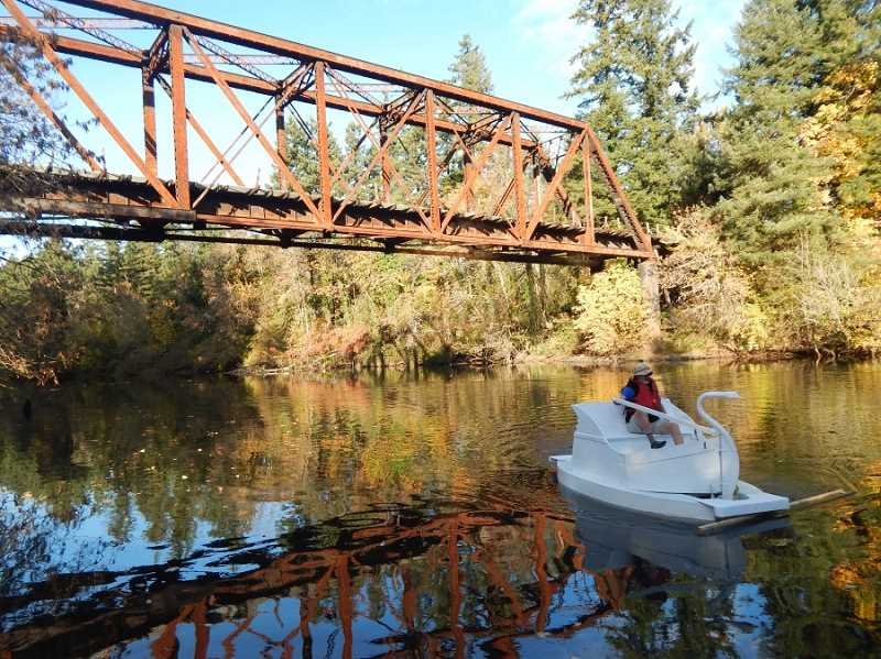 BARBARA SHERMAN - On a glorious fall day, Charlie Stalzer peddles the restored swan boat on the Tualatin River at Tualatin Community Park with the railroad trestle in the background.