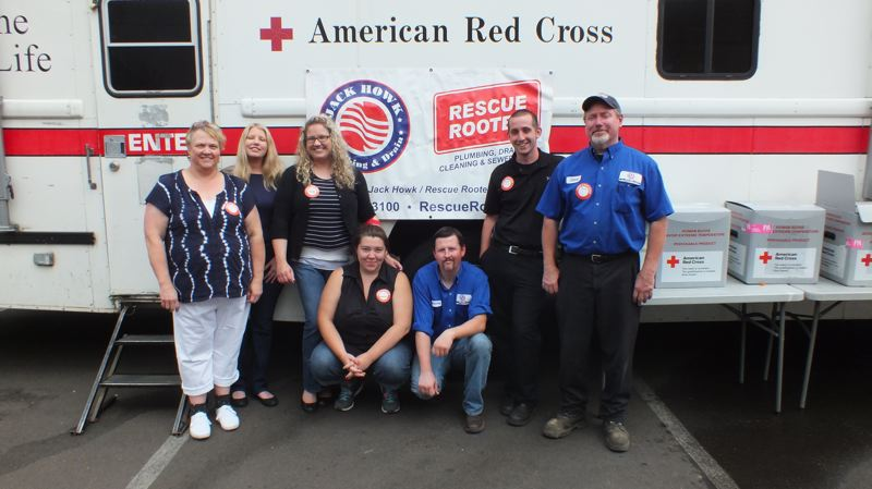 PHOTO COURTESY: JACK HOWK/RESCUE ROOTER - Employees of the Clackamas-based plumbing company pose in front of the American Red Cross bus during the last blood drive.