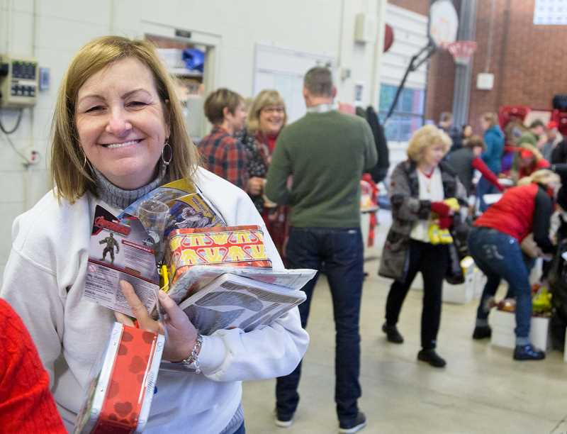 BRIAN GERATHS/FOR THE REVIEW - Terri Childress, president of the Lake Oswego Rotary Club, has her hands full with gifts for area children.