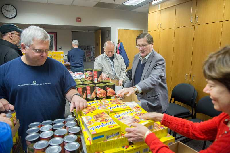BRIAN GERATHS/FOR THE REVIEW - Volunteers help assemble food baskets for Saturdays deliveries (from left): Syd Dorn, Gary Stein, Eric Allenbaugh, Bill Korach and Linda Brown.