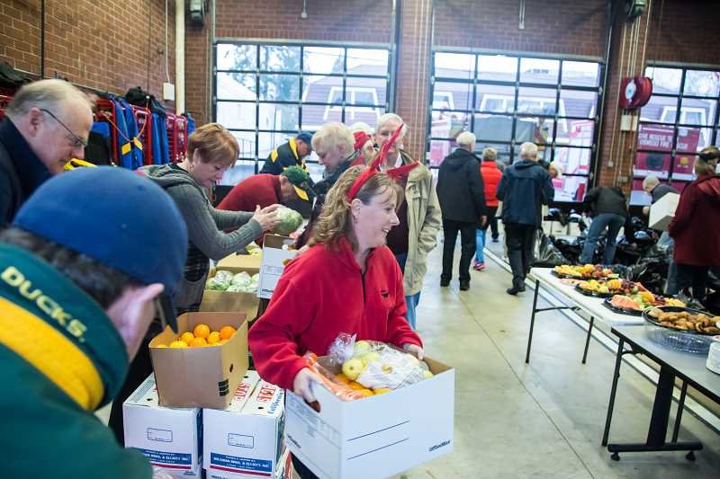 BRIAN GERATHS/FOR THE REVIEW - Cathy Geraths was among the volunteers who packed fresh produce into food and gift baskets for Lake Oswego families.