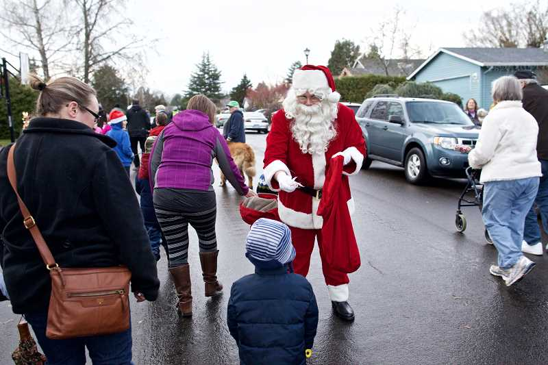 TIMES PHOTO: JAIME VALDEZ - Neighbors and visitors walk along Christmas Card Lane  to see the Christmas lights in Tigard on Friday. The city organized a community walk through neighborhoods with Christmas decorations.