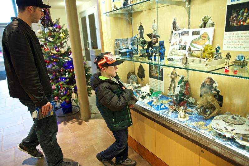 TIMES PHOTO: JAIME VALDEZ - Zack Nell of Tualatin watches his son, Carson, 7, look at the Star Wars display at the Tualatin Library. Carson enjoyed 'The Force Awakens.' He said his favorite part of the movie was the villain, Kylo Ren.
