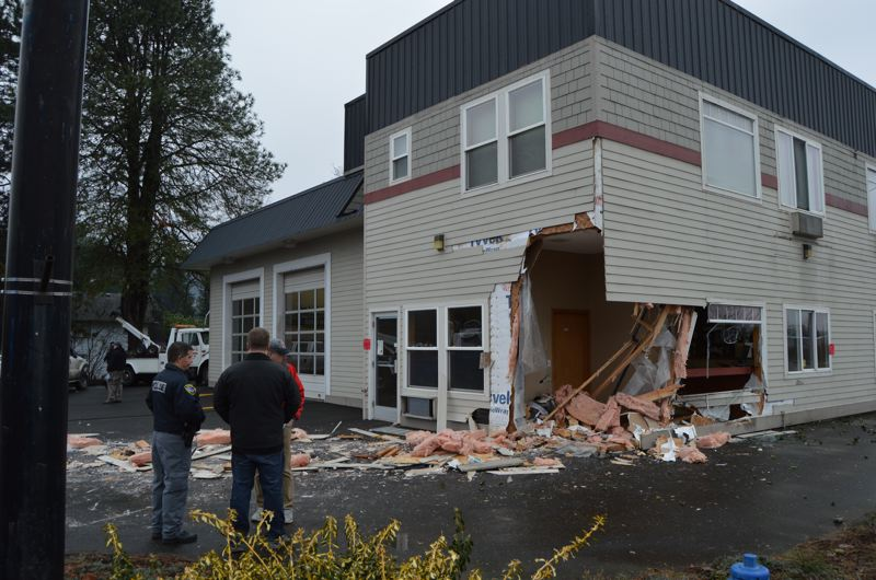 SPOTLIGHT PHOTO: NICOLE THILL - Scappoose Police Chief Norm Miller talks to Than Tussing and Loren Gramson, owners of Fast Lube and Oil, in front of their damaged storefront Monday, Dec. 28. A white pickup truck crashed into the building Monday, ripping open the side of the building leaving the lobby area exposed.