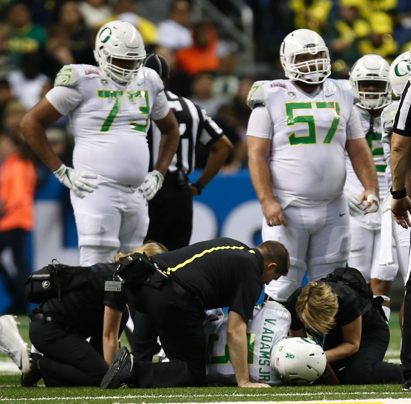 COURTESY: ANDY NELSON/THE REGISTER-GUARD - Oregon quarterback Vernon Adams Jr. is attended to by Oregon medical staff after taking a hit during the second quarter.