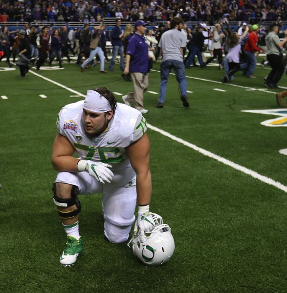 COURTESY: CHRIS PIETSCH/THE REGISTER-GUARD - Oregon's Jake Pisarcik kneels on the field as TCU fans and players celebrate their triple overtime win over the Ducks.