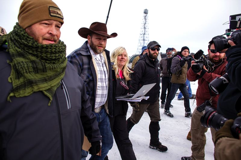 TRIBUNE PHOTO: ROB KERR - Ammon Bundy, with his bodyguard, left, and Shawna Cox, talk with reporters Monday Jan. 4, at the Malheur National Wildlife Refuge Headquarters. Bundy and a group of amed protestors have occupied of the facilities to call attention to the needs of local ranchers.