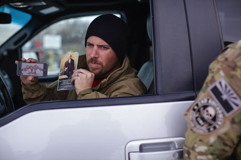 PAMPLIN MEDIA GROUP PHOTO: ROB KERR - Militiaman Jon Ritzheimer, 32, shows a photo of his wife and children and a copy of the U.S. Constitution while sitting guard in a Ford pickup truck Monday morning Jan. 4, at the Malheur National Wildlife Refuge 30 miles from Burns. He is part of a group of armed protesters occupying the wildlife refuge buildings.