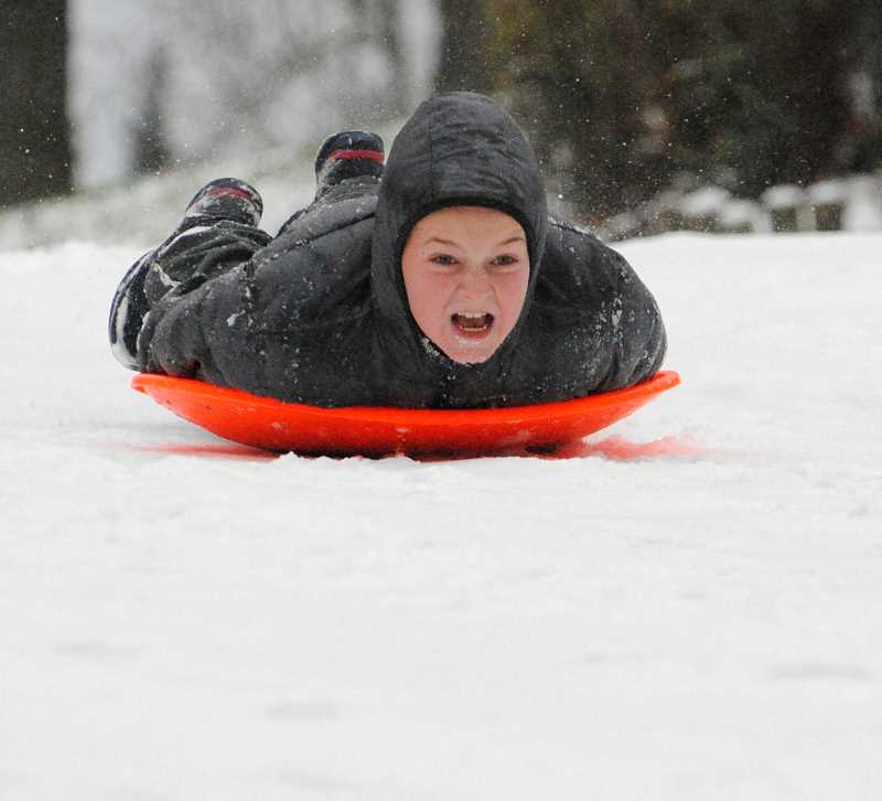 PHOTO COURTESY SARAH MORRIS - John Morris, age 10, gets serious about fun after the snow fell in West Linn last week.