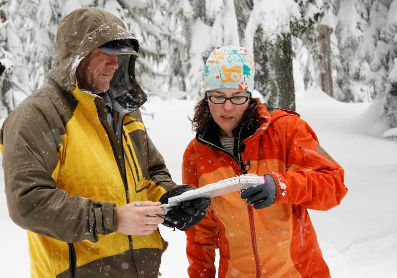 POST PHOTO: KYLIE WRAY - Dan Fries, an Oregon Snow Survey hydrologic technician, and hydrologist Julie Koeberle compare manual measurements to data aquired from equipment at the Mt. Hood SNOTEL site.