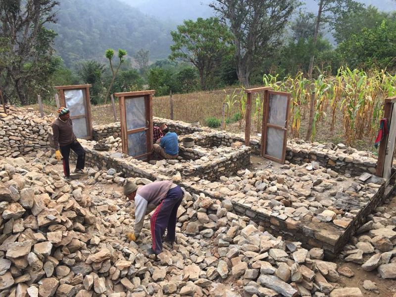 SUBMITTED PHOTO - Workers remove rubble from the remains of the school in Darbung, Nepal. Students displaced by the earthquake are attending classes in temporary bamboo structures with corrugated roofs.
