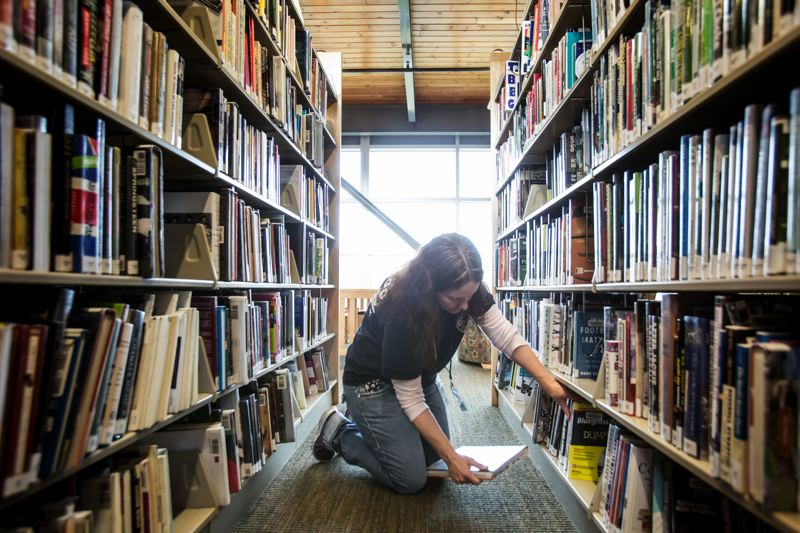 TIMES PHOTO: JONATHAN HOUSE - Megan Miller, a Tigard Library volunteer, shelves books on Thursday, Jan. 7.