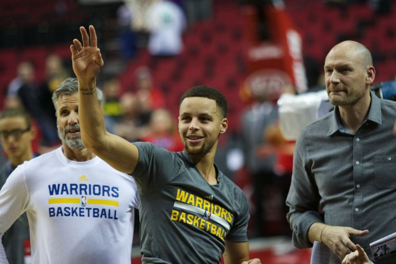 TRIBUNE PHOTO: JAIME VALDEZ - Stephen Curry (center) of the Golden State Warriors waves to fans at Moda Center before Friday night's game against Portland.