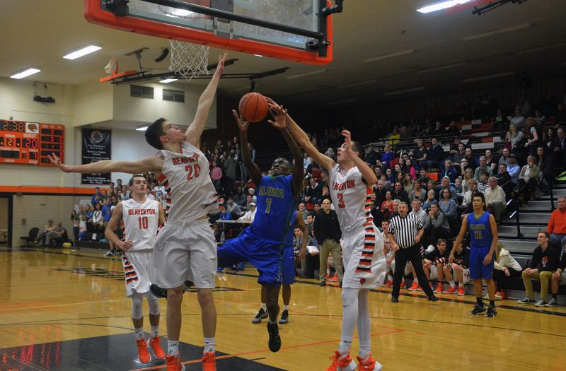 TIMES PHOTO: MATT SINGLEDECKER - Beaverton;s Beau Sheeran and Niko Bevens try to block Aloha's Marc Tshala's shot at the rim in the first quarter of the Beavers win over Aloha on Friday.