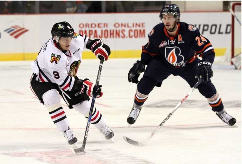 COURTESY: BRYAN HEIM/PORTLAND WINTERHAWKS - Rihards Bukarts (left) of the Portland Winterhawks keeps the puck away from Kamloops defenseman Ryan Rehill during Saturday night's game at Moda Center.