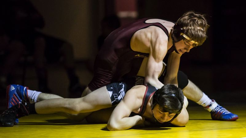 JOHN LARIVIERE - Milwaukie freshman Bryant Smith breaks down Sandy sophomore 120-pounder Hunter Rickman.