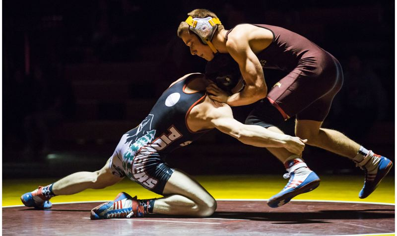 JOHN LARIVIERE - Milwaukie freshman Matthew Lee (right) battles Sandy senior 138-pounder Steven Patton.