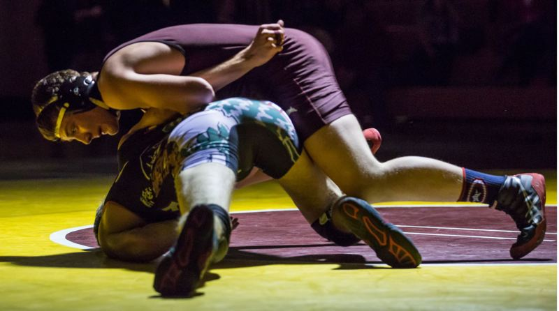JOHN LARIVIERE - Milwaukie sophomore Chazz Amundson rides Sandy 182-pound junior Abe Mitchell.