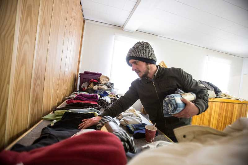 TIMES PHOTO: JONATHAN HOUSE - Nick Luttrell, a Tigard homeless man, looks through coats and blankets at the new day center at Tigard Fourquare Church, on Pacific Highway. The day center is open Thursdays from 10 a.m. to 2 p.m.