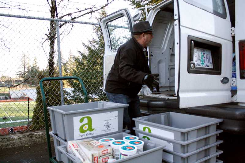 POST PHOTO: KYLIE WRAY - Sandy Community Action Center volunteer Ross Snell loads bins of fresh produce from the Sandy Safeway store into the centers van to be delivered to the local food pantry. The store donated 12,800 pounds of food in December.