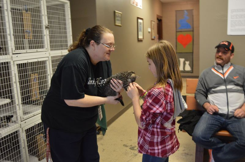 COURTNEY VAUGHN - Kristy Bills (left), a volunteer with the Columbia Humane Society, holds a kitten for 9-year-old Lily Sparks to pet.